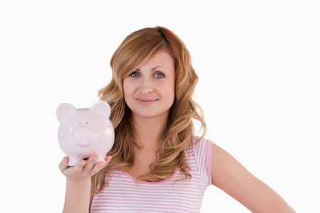 Cute blond-haired woman posing while holding her piggybank on a white background photo