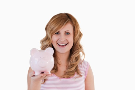 Attractive blond-haired woman posing while holding her piggybank on a white background photo