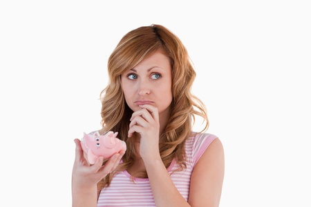 Blond-haired woman perplexed concerning her broken piggybank on a white background photo