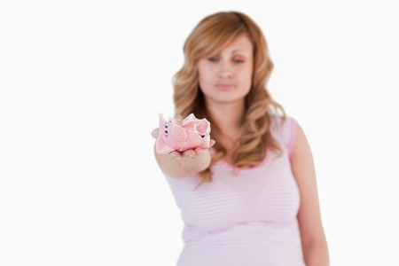 Cute blond-haired woman showing her broken piggybank on a white background Stock Photo - 10194238