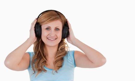 Attractive blond-haired woman listening to music standing on a white background photo