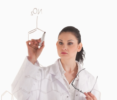 Dark-haired woman writting a formula on a white board in a lab photo