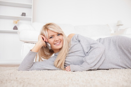 Attractive blond woman talking on cell phone lying down on a carpet in the living room Stock Photo - 10205908