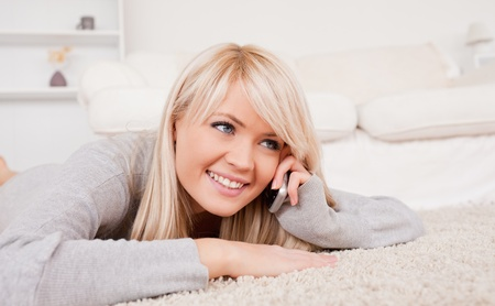 Attractive smiling blond woman talking on cell phone lying down on a carpet in the living room photo