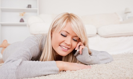 Attractive blond woman talking on cell phone lying down on a carpet in the living room Stock Photo - 10198937