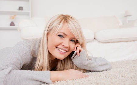 Attractive happy blond woman talking on cell phone lying down on a carpet in the living room Stock Photo - 10198529