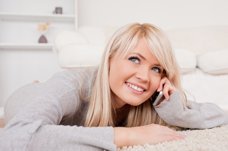 Beautiful happy blond woman talking on cell phone lying down on a carpet in the living room Stock Photo - 10191624