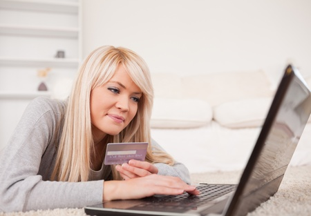 Pretty relaxed woman relaxing on laptop lying on a carpet in the living room photo