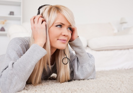 Beautiful blond woman with headphones lying on a carpet in the living room photo