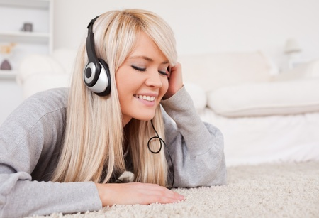 Prettyl blond woman with headphones lying on a carpet in the living room photo