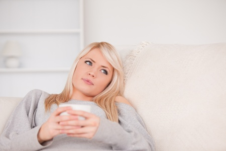 Attractive blond woman lying on a sofa relaxing on a line of tablet computers in the living room photo