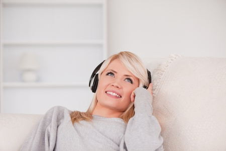 Pretty blond woman with headphones lying in a sofa in the living room photo