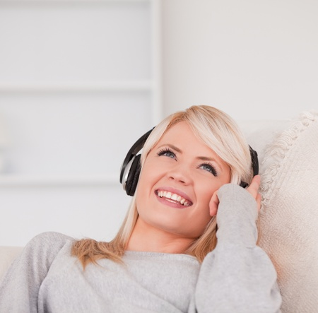 Pretty young blond woman with headphones lying in a sofa in the living room photo