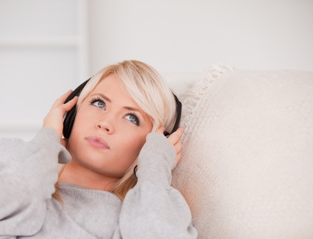 Attractive young blond woman with headphones lying in a sofa in the living room photo