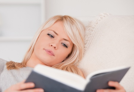 Concentrated blonde woman reading a book while lying on a sofa in her appartment photo