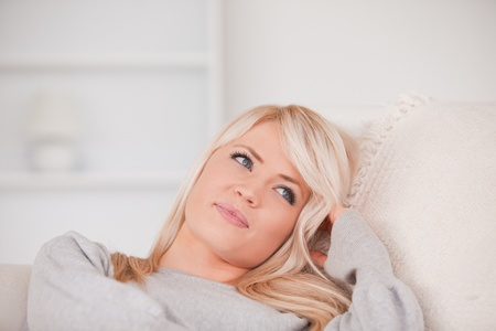 Portrait of a happy blonde woman relaxing while lying on a sofa in her appartment photo