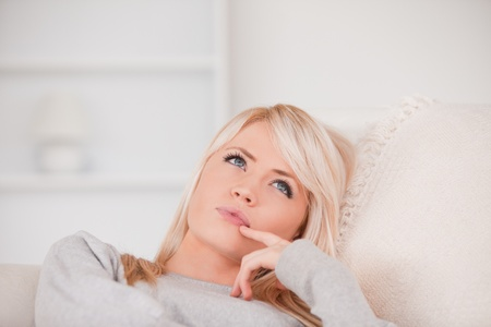 Portrait of a pensive blonde woman lying on a sofa in her appartment photo