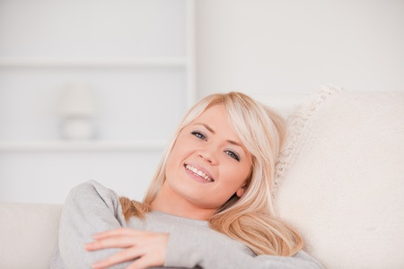 Smiling blonde woman lying on a sofa in her appartment photo