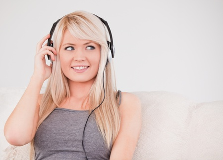 Beautiful young blond woman with headphones sitting in a sofa in a studio photo