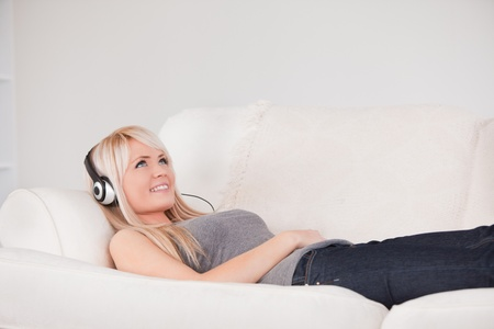 Smiling young blond woman with headphones lying in a sofa in a studio photo