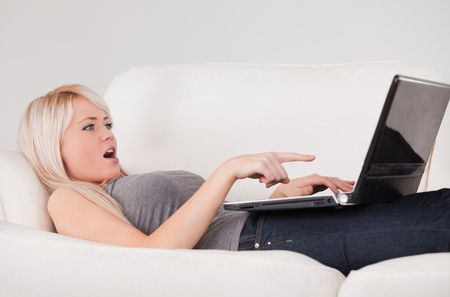 Surprised woman relaxing on laptop lying on a sofa in a studio photo