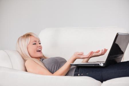 Joyful woman relaxing on laptop lying on a sofa in a studio photo