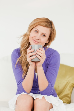 Attractive red-haired woman holding a cup of coffee and posing while sitting on a sofa in the living room photo