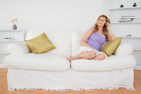 Beautiful red-haired woman on the phone sitting on a sofa in the living room Stock Photo - 10198335