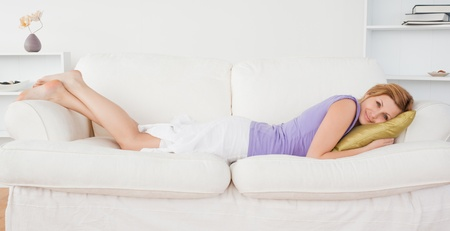 Attractive woman posing and smiling while lying on a sofa in the living room photo