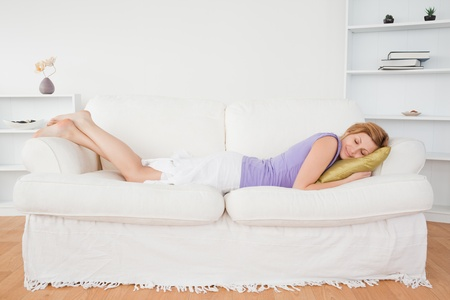 Attractive woman taking a rest lying on a sofa in the living room photo