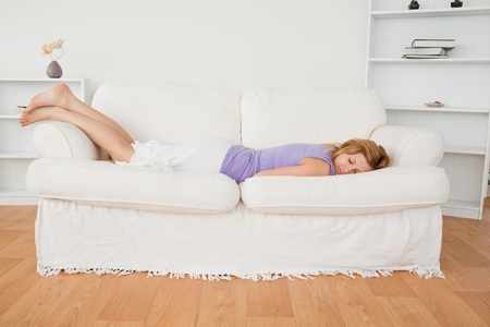 Attractive woman sleeping while lying on a sofa in the living room photo