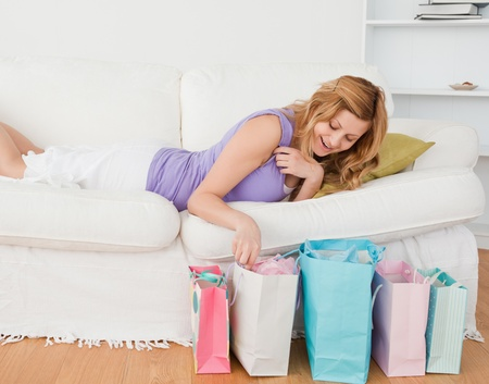 Attractive blond-haired woman lying on the couch having done her shopping photo
