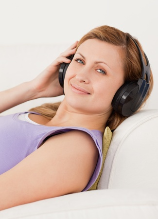 Attractive blond-haired woman listening to music lying on the sofa in the living-room photo