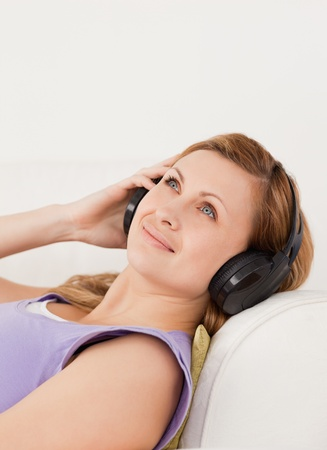 Cute blond-haired woman listening to music lying on the sofa in the living-room Stock Photo - 10197737
