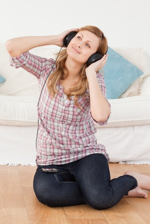 Cute woman listening to music while sitting on the floor in the living-room photo