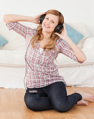 Blond-haired woman listening to music while sitting on the floor in the living-room photo