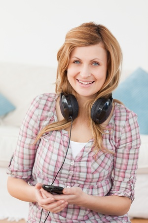 Happy blond-haired woman with headphones and mp3 player sitting in the living-room photo