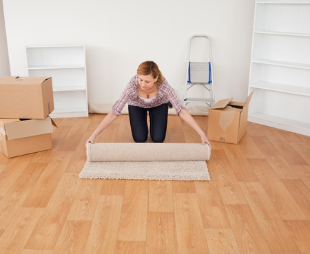 home moving: Blond-haired woman rolling up a carpet to prepare to move house  Stock Photo