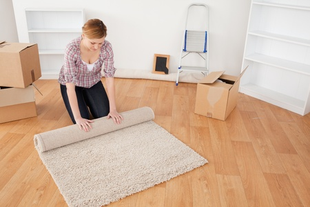 Cute woman rolling up a carpet to prepare to move house  photo