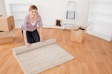 Attractive woman rolling up a carpet to prepare to move house  photo