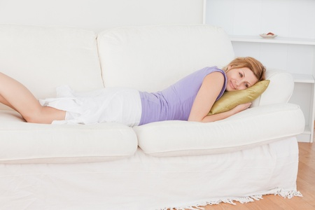 Cute blonde woman resting while lying on the sofa in the living-room photo