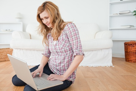 Attractive woman surfing on her laptop sitting on the floor Stock Photo - 10206437