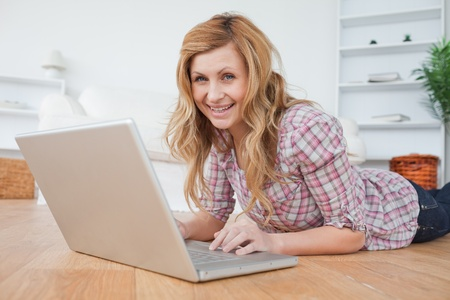 Blond-haired woman looking at the camera while chatting on her laptop in her appartment photo