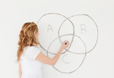Blond-haired teacher drawing a scheme on a white board in a classroom photo