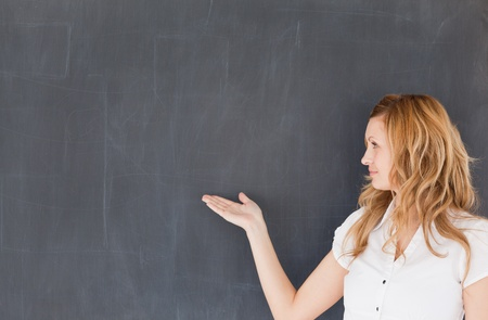 Attractive teacher showing an empty blackboard in a classroom photo