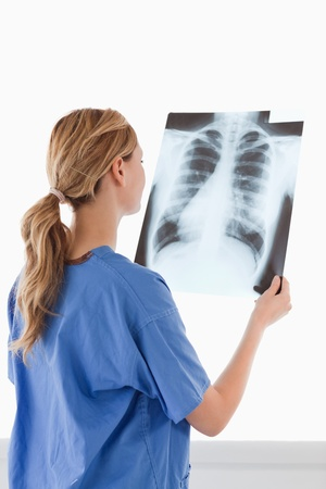 Cute female doctor looking at an X-ray on a white background Stock Photo - 10198076