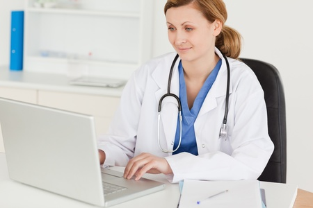 doctor laptop: Attractive female doctor working on her laptop in her surgery Stock Photo