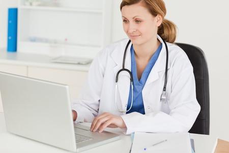 medico computer: Attraente dottoressa lavorando al suo computer portatile nel suo intervento