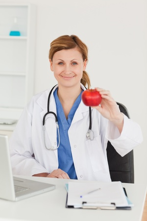 Cute female doctor showing an apple to the camera in her surgery photo