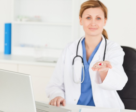 Beautiful female doctor showing pills to the camera while sitting in her office photo